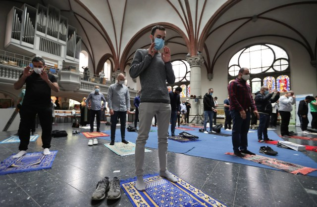Muslims pray inside the evangelical church of St. Martha's parish, during their Friday prayers, as the community mosque can't fit everybody in due to social distancing rules, in Berlin, on May 22, 2020. (Reuters)