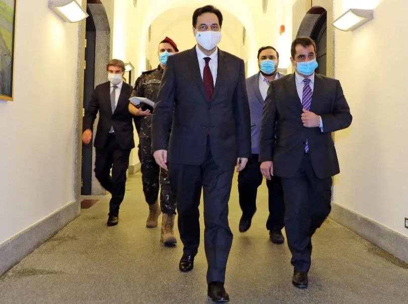 Lebanese Prime Minister Hassan Diab (C) walking while wearing a face mask ahead of an emergency cabinet session in Beirut on June 12, 2020. (AFP)