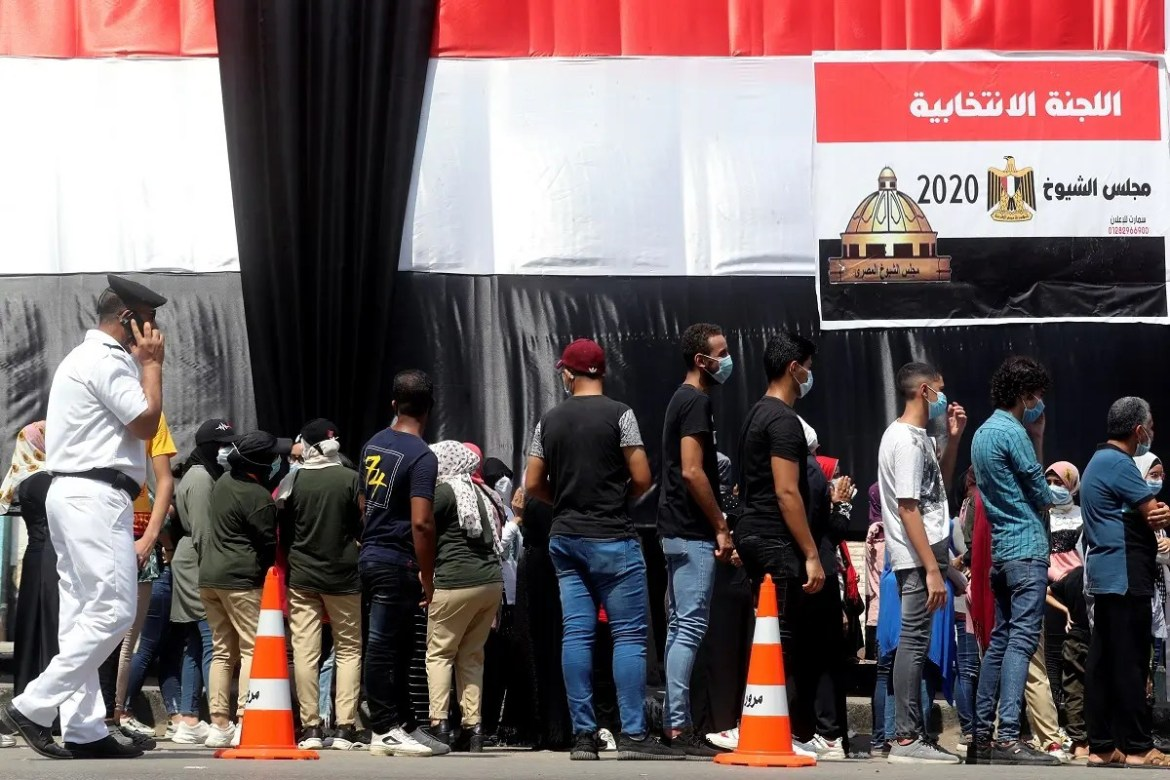 People wait in line to cast their votes outside a school used as a polling station during Egypt's senate elections in Cairo, Egypt, August 11, 2020. (Reuters)