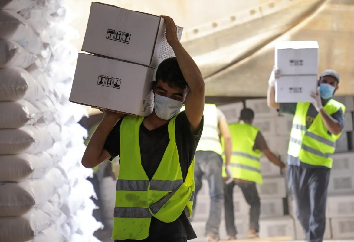Workers carry boxes of humanitarian aid near Bab al-Hawa crossing at the Syrian-Turkish border, in Idlib governorate, Syria, on June 30, 2021. (Reuters)