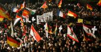 Supporters of anti-immigration movement Patriotic Europeans Against the Islamisation of the West (PEGIDA) hold flags during a demonstration in Dresden