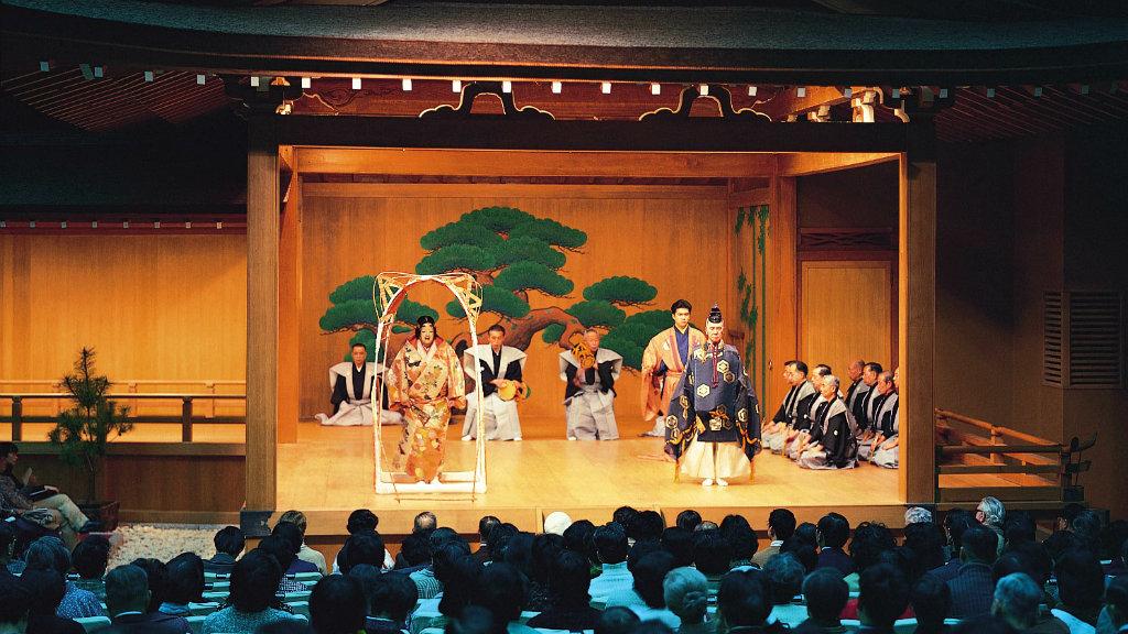 Cultura Japonesa - O ator no palco com orquestra e coro