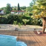 Terrasse bois en pin en abords de piscine avec rive courbe en inox. Massif d'agrément surfacé gravier