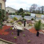 Massif minéral d'entrée avec rivière de galet, surfaçage brique et pouzzolane, graminées et plantes persistantes à faible développement
