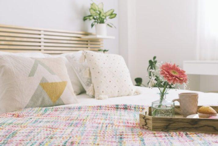 Cama tendida con flores