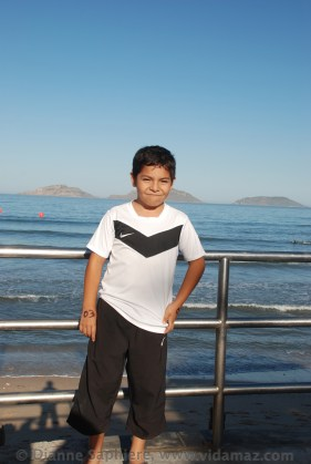 Luisito Zazueta, at eight years old the youngest boy ever to complete the Travesía Anual, the 5.6 km swim to Deer Island, behind him in the photo.
