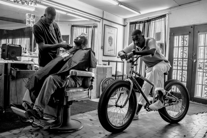 a man on a bike in a barber shop in Robert LeBlanc A New America