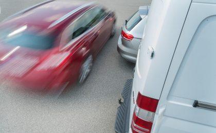 Der Autofahrer will rückwärts ausparken und kann den fließenden Verkehr kaum sehen - in solchen Fällen helfen Radarsensoren und können vor Gefahren warnen.