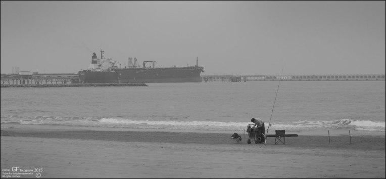 Pescador en playa gris