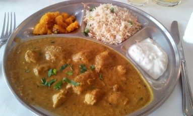 The close-up of the lunch menu: chicken curry, polenta, rice and yogurt sauce