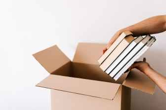 crop man packing stack of books in opened cardboard box