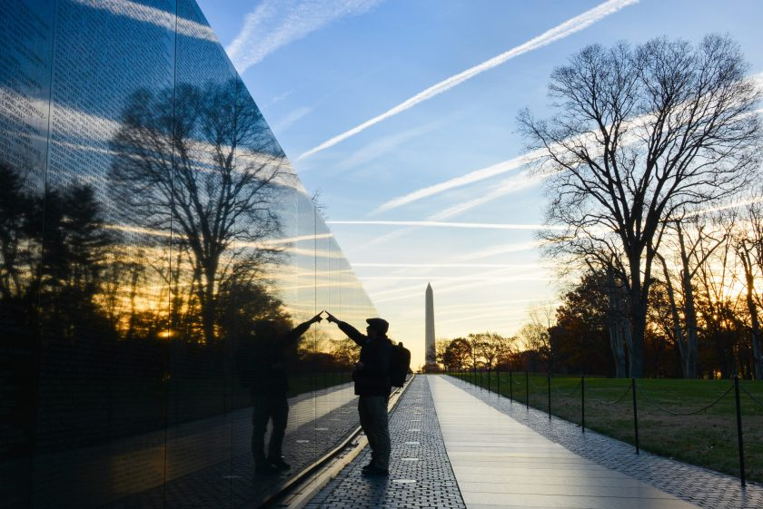 Washington DC - A Veteran looks for a name at Vietnam Veterans Memorial Wall at sunrise