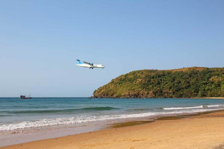 An airplane is landing close to the beach