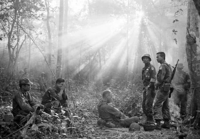 Sunlight breaks through dense foliage around the town of Binh Gia as South Vietnamese troops, joined by US advisers, rest after a tense night of waiting in an ambush position for a Vietcong attack that did not come, January 1965 Photograph: Horst Faas/AP