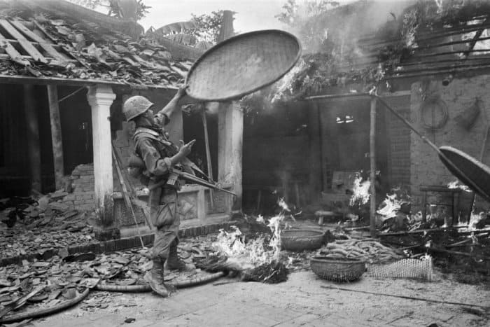 A 1st Cavalry Division soldier throws a rice basket on to the flames as his unit sweeps through a village near Tam Ky, 350 miles north-east of Saigon, on 27 October 1967. A peasant woman had tried to salvage the basket from the burning house, but US troops were intent on destroying anything that might be of value to the Vietcong Photograph: Dang Van Phuoc/AP