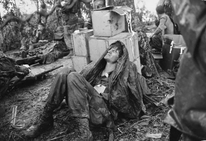 A US paratrooper, wounded in the battle for Hamburger Hill, grimaces in pain as he awaits medical evacuation at base camp near the Laotian border on 19 May 1969 Photograph: Hugh Van Es/AP