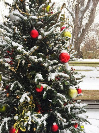 Closeup of a naturally decorated Christmas tree in the snow