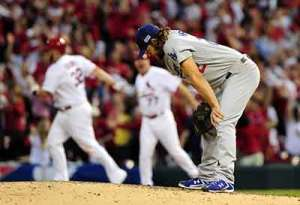 Matt Adams rounds first on a homer off Clayton Kershaw. Kershaw is sad in the foreground.