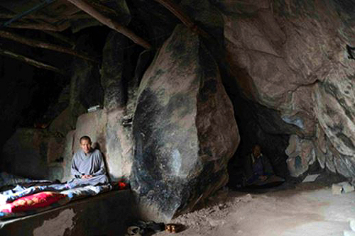 Two Buddhist monks meditating in their cave dwelling