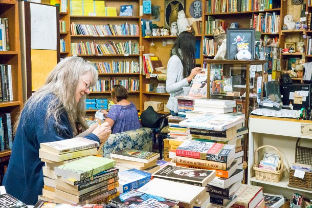 Dianne Thi Nguyen / Staff Photographer spot the owls:  Vera Lee prices and prepares a new inventory of books to add to the already massive collection. Owls are peppered around the store, camouflaged among the books.