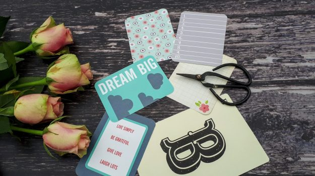 postcards a black wooden background, scattered around one says Dream Big, another 'Live Simply, Be Grateful, Give Love, Laugh Lots', another a 1-10 list on a grey background, A large letter B card, four orange/yellow roses and a pair black garden snipper sissors