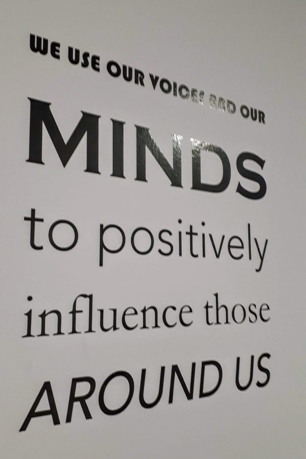 sign saying we use our voices and our minds to positively influence those around us