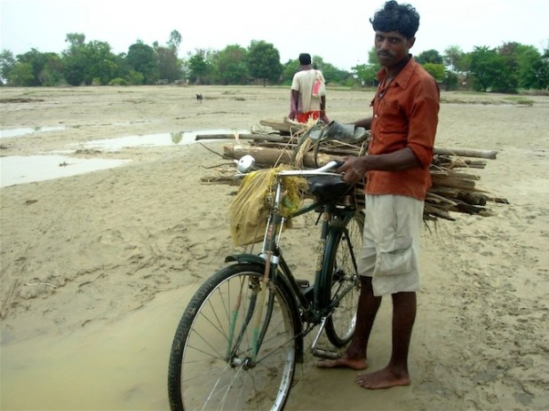 A farmer cycles near his now waterlogged farm. (Photo by Naresh Newar/IRIN)