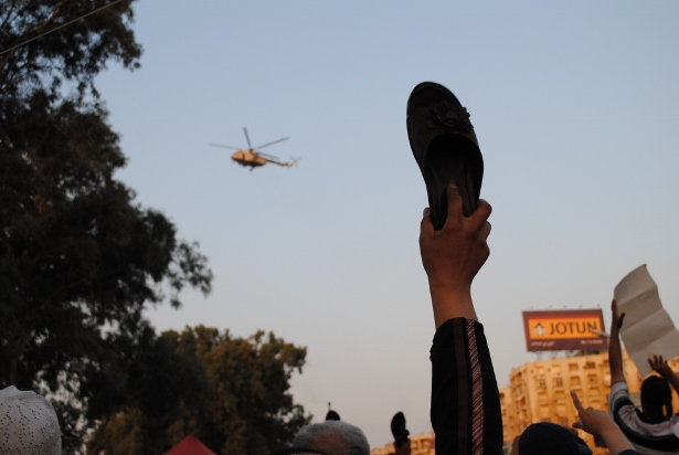 An Egyptian protester raises a shoe to the sky as a military helicopter flies overhead. (Photo by Jihad Abaza via WNV)