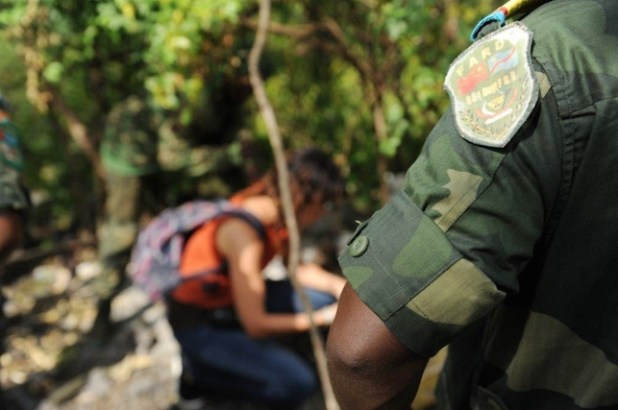 An investigator with the NGO, Conflict Armaments Research, sifts through bullets left behind at an armed group's base, after the DRC national army over ran the position in the Virunga National Park. (Photo by Guy Oliver/IRIN)