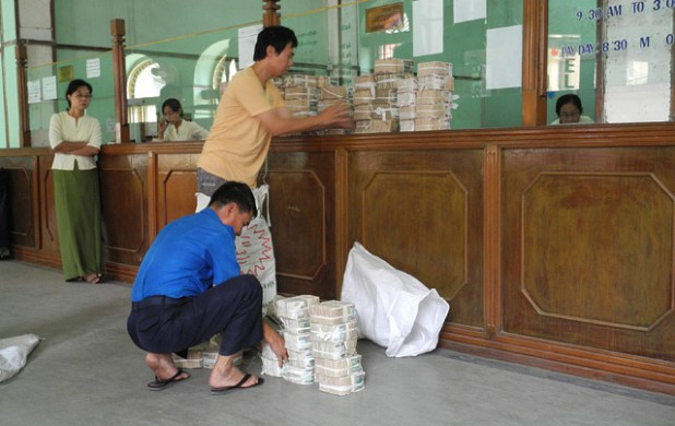 Customers making deposit at a bank in Yangon. Despite promising economic potential, the country's currency remains far from stable. (Photo by Axel Drainville, Creative Commons License)