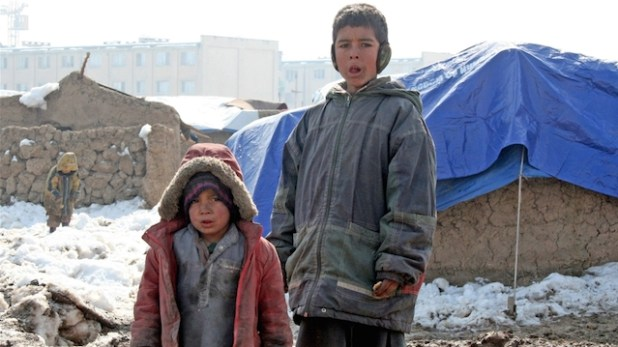 Two IDP children from southern Helmand province standing behind their mud hut on the outskirts of Kabul. (Photo by Mohammad Popal/IRIN)