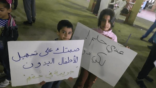 """More than 1,000 stateless children in Kuwait are not allowed to go to school. """"Your silence on preventing Bidoon children access to education is a crime,"""" reads the placard on the left. The other one reads: """"I have a dream. But I am Bidoon."""" (Photo shared on Twitter by @nawaf_alhendal)"""