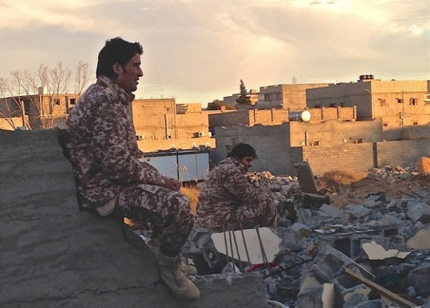 Dusk in the Libyan town of Ben Jawad, where two soldiers from forces operating under the Tripoli-based government sit by the rubble of another flattened home. The front-line, near Es Sidra oil port, is just 30 kilometres away.  (Photo by Tom Westcott/IRIN )