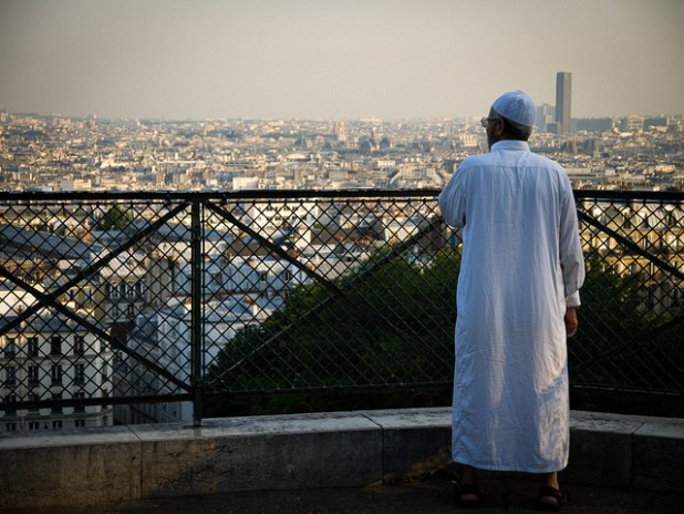 A French Muslim looks at the city below while standing atop Montmartre. (Photo by Francisco Osorio, Creative Commons License)