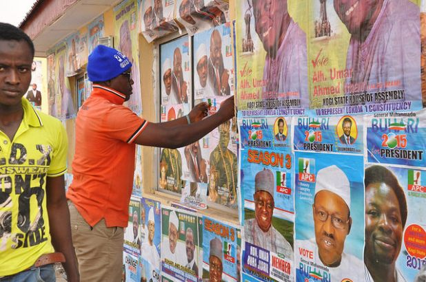 An election worker plasters posters ahead of elections in Nigeria. (Photo by Heinrich-Böll-Stiftung, Creative Commons License)