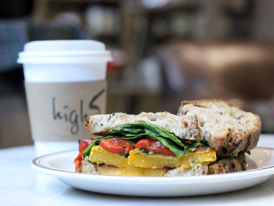 A veggie sandwich on a plate with a high5 coffee cup behind