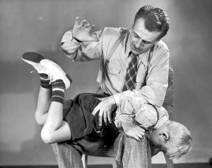 Father spanking son (5Ð7) on lap (B&W). RightsÐmanaged.  Getty Images Prestige