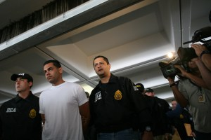 Drug Enforcement Administration officers escort a handcuffed suspect after his arrest on drug smuggling charges in San Juan, Puerto Rico, Wednesday, June 6, 2012. U.S. federal agents say they raided Puerto Rico's international airport and other areas early Wednesday, arresting at least 33 people suspected of smuggling millions of dollars' worth of drugs aboard commercial flights. (AP Photo/Ricardo Arduengo)