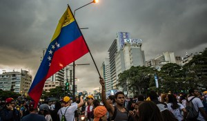 A man waves a Venezuelan flag during a demonstration by a group made up of mostly students in Caracas, Venezuela, on Monday, Feb. 17, 2014. Venezuela's government said it will import $1 billion of food and medicine to guarantee supplies for four months as the opposition plans to march today to protest shortages and inflation. Photographer: Meridith Kohut/Bloomberg