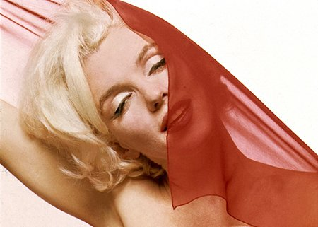 This red veil on her face and these closed eyes can symbolically portray Marilyn's sacrifice by the industry.