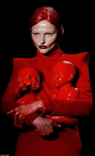This model holds two dolls covered in fake blood. A sickening way to represent child sacrifice.