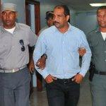 El alcalde de Bayaguana, Nelson Osvaldo Sosa (Opi) sostenido por dos agentes de la Policía Nacional.