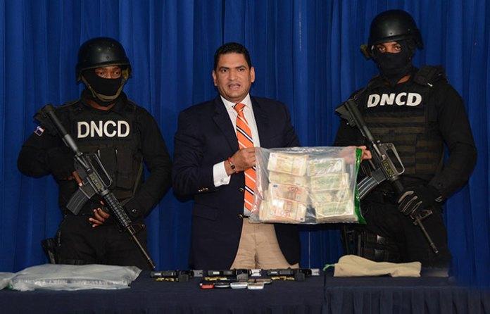Miguel Medina, vocero de la DNCD presenta los dólares y euros incautado a cuatro alegados narcotráficantes.