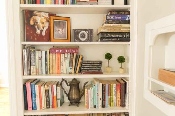 Books, photos, and mementos on the built-in bookcase in the hallway.