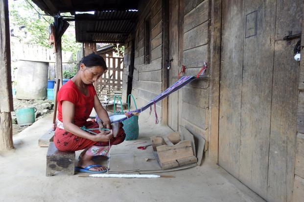 Khrolou Ngatsi weaving a table runner on the porch of her hut.