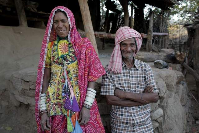 Mansa Ram 55 and his wife Hansi Bai, stand at the front of their small dwelling in the village of Kayarakhet, Udaipur. Hansi is dressed in her traditional stitched clothes, once made by hand, now made on a machine.
