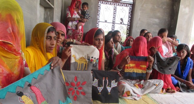 Women embroiders show their latest work after a training workshop.