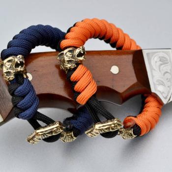 Фото двухцветный плетеный браслет из паракорда с застежкой молот Тора и бусиной волк