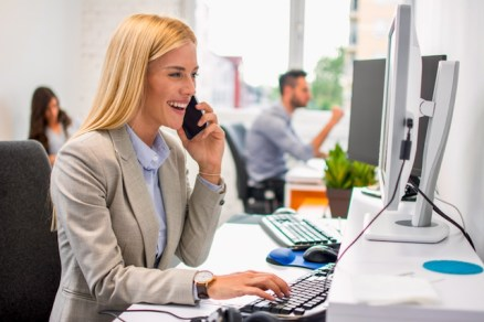 Smiling business woman working on computer and talking on mobile phone in office