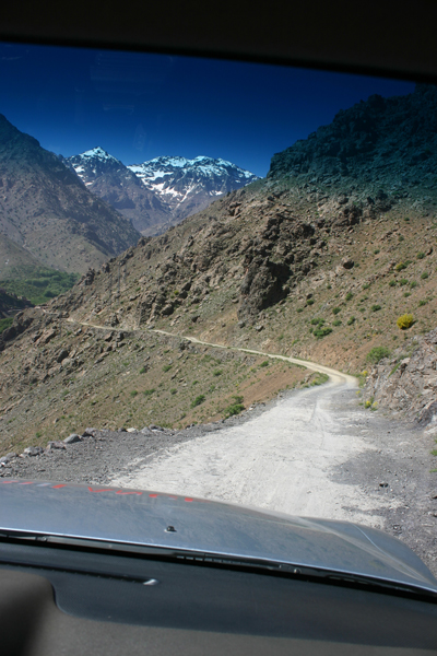 View through ambulance windscreen of winding mountain road above Imlil, High Atlas Mountains, Morocco